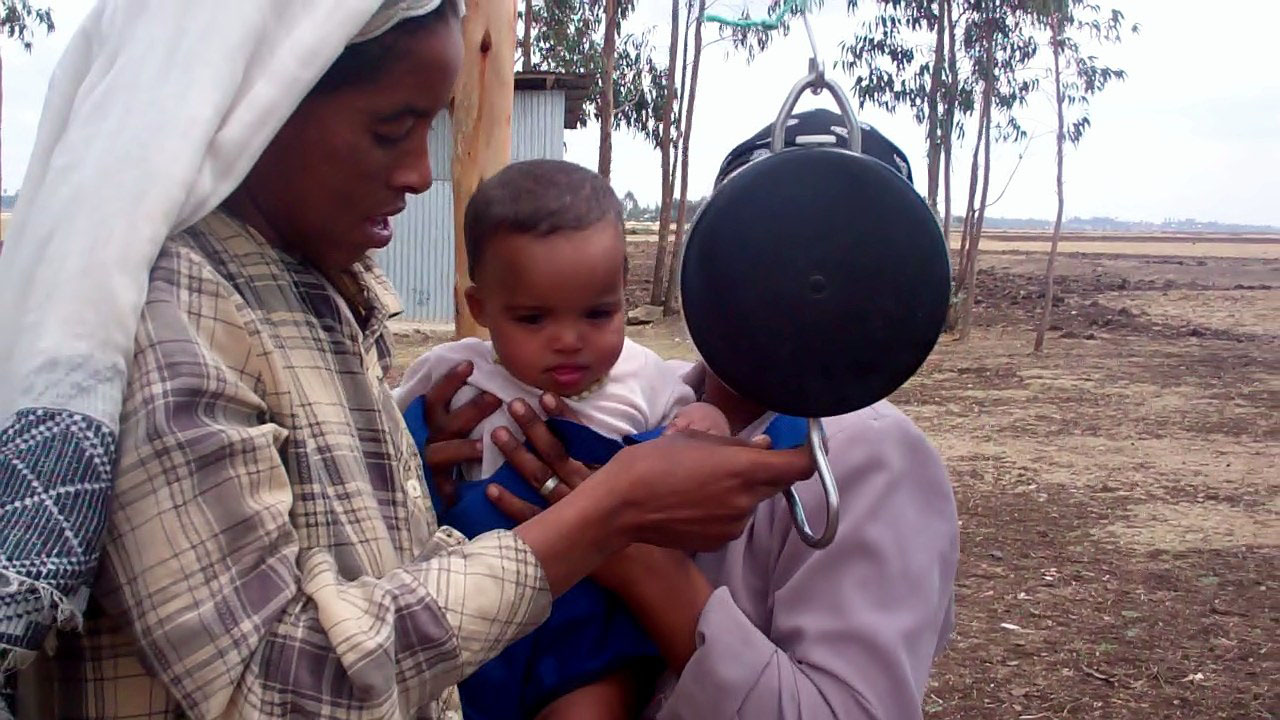 Ejegayehu weighs Meseret's daughter on a salter scale
